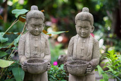 Stone sculpture of kids holding bowl Royalty Free Stock Photo
