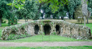 Stone sculpture of man and woman with caves and a swimming pool with water in park at Villa Pamphili in Rome, capital of Italy Stock Photos
