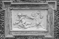 Stone sculpture picture on which two angels fight, and the two look at it in park at Villa Pamphili in Rome, capital of Italy Stock Photography
