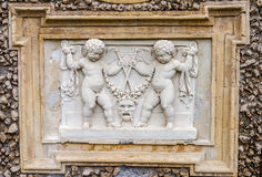 Stone sculpture picture on which two angels fight, and the two look at it in park at Villa Pamphili in Rome, capital of Italy Royalty Free Stock Photo