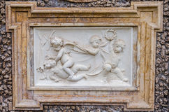 Stone sculpture picture on which two angels fight, and the two look at it in park at Villa Pamphili in Rome, capital of Italy Stock Photos