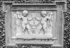 Stone sculpture picture on which two angels fight, and the two look at it in park at Villa Pamphili in Rome, capital of Italy Royalty Free Stock Image