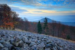 Stone of sea, scree slope landscape with blue evening sky, autumn forest. Studenec Hill in the Luzicke hory mountains, Czech repub Royalty Free Stock Image