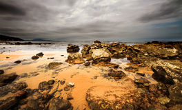 Stone sea shore. Orange sand,  overcast sky Royalty Free Stock Photography
