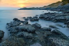 Stone in sea and wave on sunset time with long exposure at Ko Si. Chang District Chonburi, Thailand Royalty Free Stock Photography