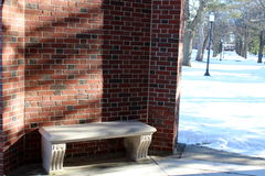 Stone seat in curve of brick wall Stock Images