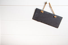 Stone sign hanging on door. Black stone slate blank sign hanging on white wooden door Stock Image
