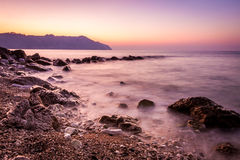 Stone and silky waves at sunset - nature background Royalty Free Stock Images