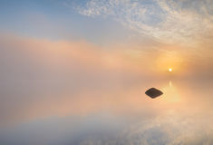 Stone. Single stone in the water with the sun coming up in the background Royalty Free Stock Photos