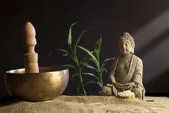 Stone sitting buddha and Tibetan bowl Stock Photos