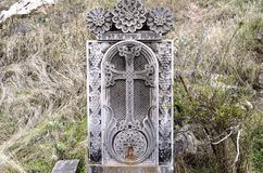 The stone slab with the cross and tap forwater Royalty Free Stock Photography