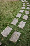 Stone slabs pathway. A path created by placing stone slabs on the grass Royalty Free Stock Image