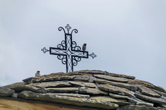 Stone slate-roof of old medieval church with cross in restored Montenegrin or Giginski monastery. St. St. Cosmas and Damian, mountain  Kitka, Breznik, Pernik Royalty Free Stock Photo