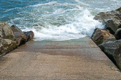 Stone slipway with blue ocean sea breaking waves and rocks Royalty Free Stock Photo
