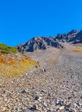 Stone slope of the volcano with walking tourists. Royalty Free Stock Photography