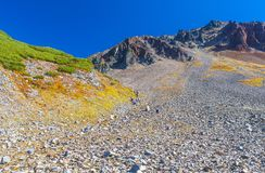 Stone slope of the volcano with walking tourists. Royalty Free Stock Photos