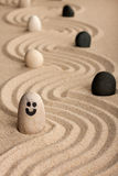 Stone smiley sticking out of the sand, between white and black stones Stock Photo