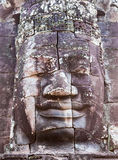 Stone smiling face in Prasat Bayon, Angkor, Cambodia. Stone smiling face in Prasat Bayon, part of Angkor Khmer temple complex, among tourists ancient landmark Royalty Free Stock Photography