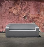 Stone sofa cracked plaster wall Royalty Free Stock Image