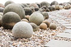 Stone sphere in garden with footpath Royalty Free Stock Image