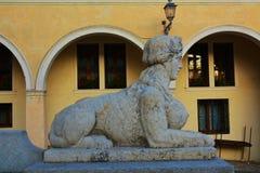Stone sphinx, in Conegliano Veneto, Treviso, Italy. Stone sphinx statue, cityscape and the Accademy Theatre, in Piazza Cima, in Conegliano Veneto, Treviso Royalty Free Stock Photos