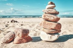 Stone stack on a beach, zen like natural background. Retro toned picture of a stone stack on a beach, zen like natural background Royalty Free Stock Image