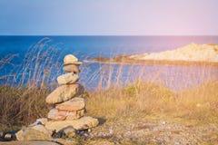 Stone stack on coastline blue ocean stock images