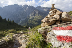 Stone stack next to hiking trail in Alps. Stack of stones placed next to hiking path in Tyrol,  mountain range of Hochgall in background, Austrian/Italian Alps Royalty Free Stock Image