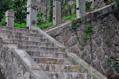 Stone stair in devious and upward. Aged stone and concrete made stair atttached with vine plant, with hand post and rail, shown as aged color and texture,  in Stock Photography