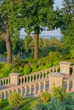 Stone staircase with decorative handrails on the background of the green park zone and blue pond. For your design stock photos