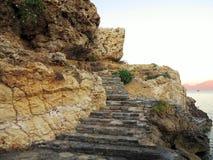 Stone staircase ladder on rocks near sea in Greece Stock Photo