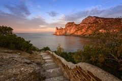Stone staircase leading to the sea. With a rock at sunset Royalty Free Stock Photos