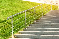 Stone staircase leading up the slope with lawn grass, with metal shining and railing. Royalty Free Stock Images