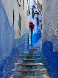 Stone staircase in a narrow aperture between the old blue walls of medina of Chefchaouen, Morocco. Stone staircase in a narrow aperture between the old blue Stock Photo