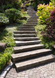 Stone staircase tiles. A stone staircase winds up a steep landscaped garden path, with a tiled step at the bottom Royalty Free Stock Photos