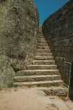 Stone staircase between wall and big rock at the Castle of Monsanto. Stone narrow staircase between wall and big rock, in a sunny day at the Castle of Monsanto stock photos