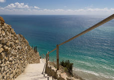 Stone stairs down to azure sea. Steep descent. Rock wall. Blue water. Stone stairs down to azure sea. Steep descent. Rock wall. Blue sparkling water. Costline of royalty free stock photos