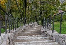 Stone stairs with a metal handrail, Checiny Castle. A stone staircase down with a metal handrail against a background of green trees, the Royal Castle in Checiny stock image