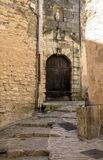 Stone stairs and old door in alley of the medieval village Gordes, Vaucluse, Provence-Alpes-Côte d`Azur, Provence,. France Royalty Free Stock Image