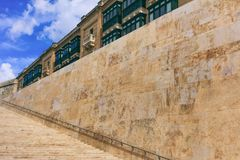 Stone stairs and wall with metal rail in the historic center of Valletta, Malta. Blue sky and traditional Maltese buildings backgr. Stone stairs and stone wall Stock Photo