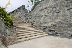 Stone stairway along aged grey brick wall Royalty Free Stock Photo