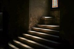 Stone stairway in dark medieval castle dungeon. With a ray of sunlight projected on the steps. Gothic atmosphere, religious ancient building, suggesting royalty free stock photo