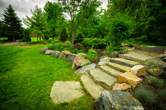 Stone Stairway on a Lush Green Garden Path. The natural stone steps of a stairway garden feature climb a small hill in a lush, green summer rock garden Royalty Free Stock Images