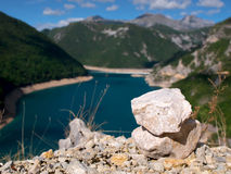 Stone stake above lake in mountains Royalty Free Stock Photography