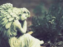 Stone statue, angel, garden decoration. Angle with wings in thoughtful position stock photos