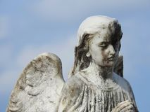 Stone statue of an angel with wings, praying. royalty free stock photo