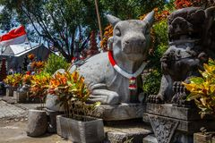 Stone statue of big cow with a garland in red and white colors and Indonesian flag for Indonesia Independence Day, Bali, Indonesia.  stock photos