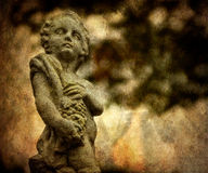 Stone Statue of Boy Holding Grapes. A stone statue of a young boy clutching grapes with a distressed photo-effect and texture added. Includes copy space for your royalty free stock image
