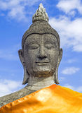 Stone statue Buddha. On blue sky background Stock Photography
