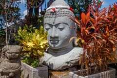 Stone statue of Buddha head with a garland in colors of Indonesian flag for Indonesia Independence Day, Bali, Indonesia. Stone statue of Buddha head with a royalty free stock images